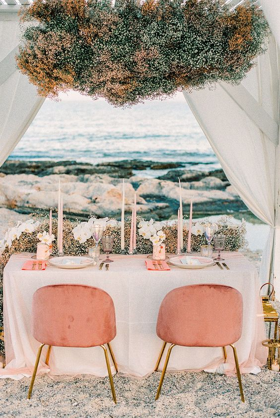 a blue, white and yellow baby's breath table runner and a chandelier are a lovely and beautiful pastel decor idea to enjoy