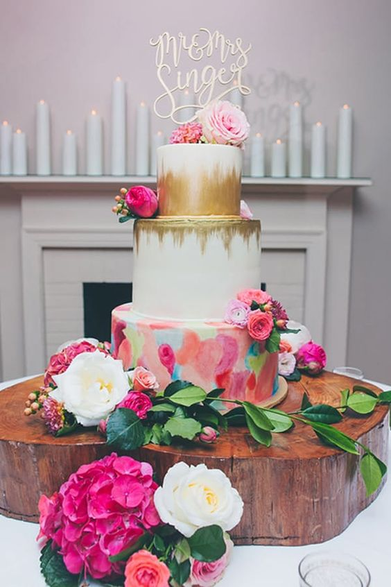a bold wedding cake with white tiers and gold leaf detailing, a bold watercolor tier and bright blooms and a calligraphy topper