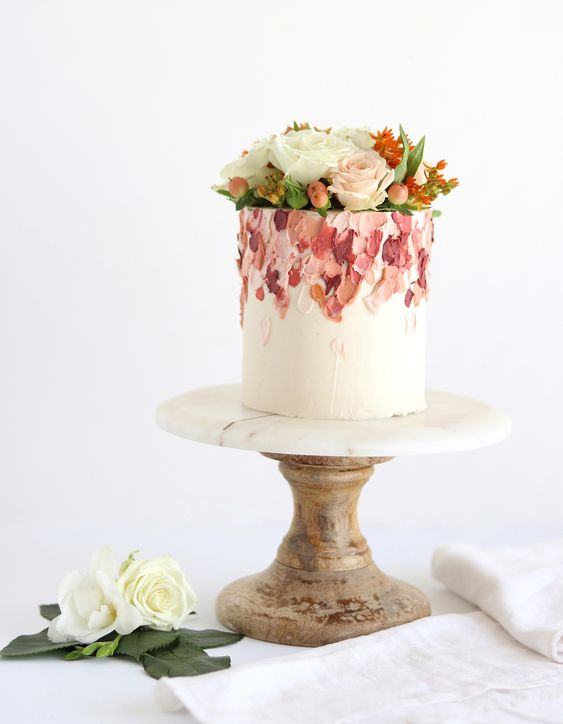 a bold white wedding cake decorated with bright brushstrokes and with fresh blooms on top for a spring or summer wedding