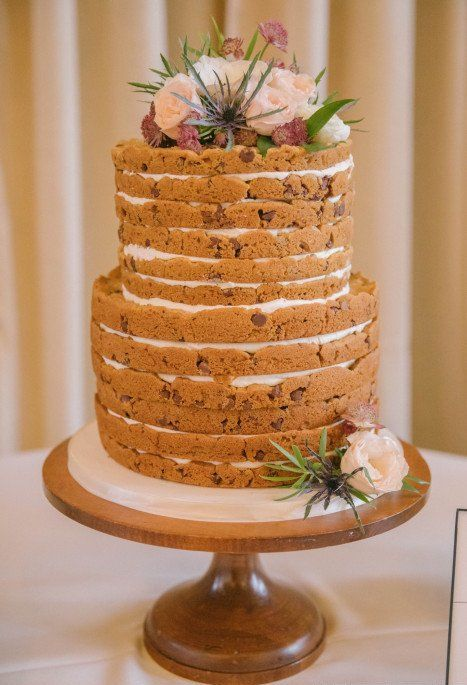 a cool cookie wedding cake with white filling, fresh blooms, thistles and greenery is a lovely idea
