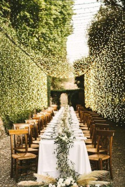 a lovely al fresco wedding reception with white blooms and greenery, pampas grass and a warm light canopy over the space