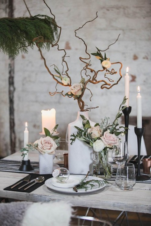 a refined Scandinavian wedding tablescape with a striped runner, black napkins, a unique branch and rose centerpiece and candles