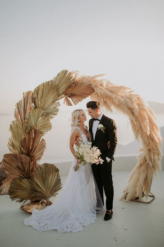 a round wedding arch partly covered with pampas gras and partly with dried fronds looks very cool and stylish