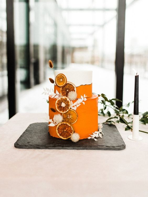 a stunning white and orange wedding cake with white dried grasses and dried citrus slices is a lovely idea for a tropical boho wedding