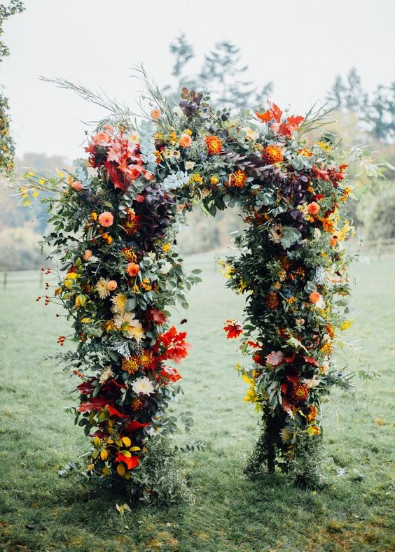 a very lush greenery and bright blooms wedding arch is a lovely idea for a 70s inspired wedding