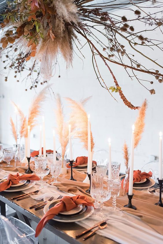 a boho wedding tablescape with a pastel runner, rust napkins, grasses, candles and a large installation with rust leaves, branches and pampas grass