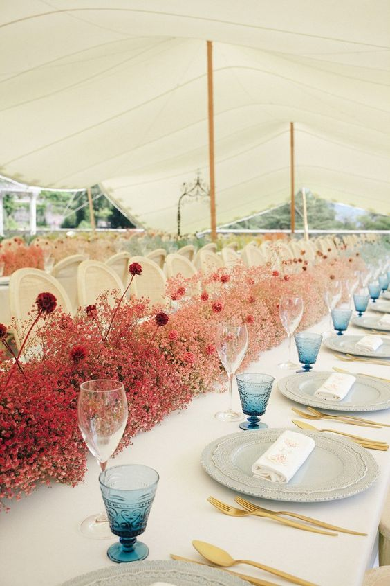 a bold pink and red baby's breath table runner with some additional blooms, contrasting blue glasses and gold cutlery for more color