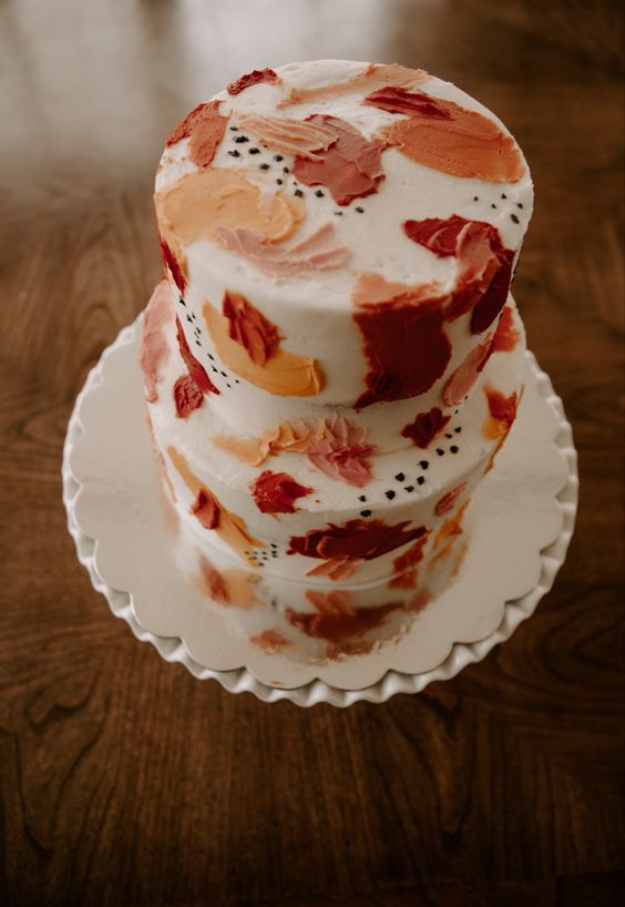 a bright wedding cake with colorful red, burgundy and orange brushstrokes and black polka dots for a mid-century wedding