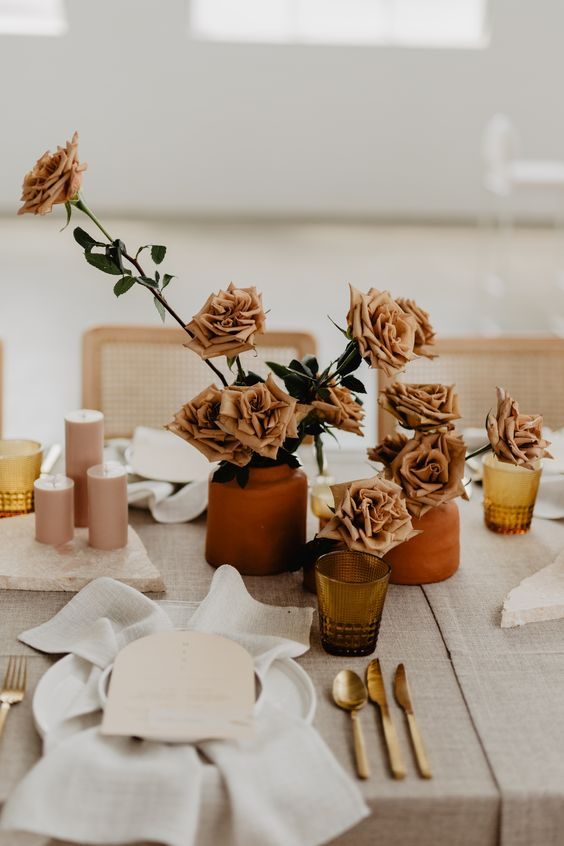 17 a chic cluster wedding centerpiece of terracotta vases with rust-colored roses and pink candles is great for a 70s wedding