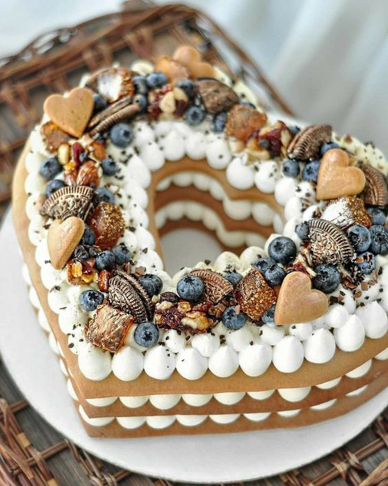 a heart-shaped cookie wedding cake topped with blueberries, mini cookies, candles and Oreos