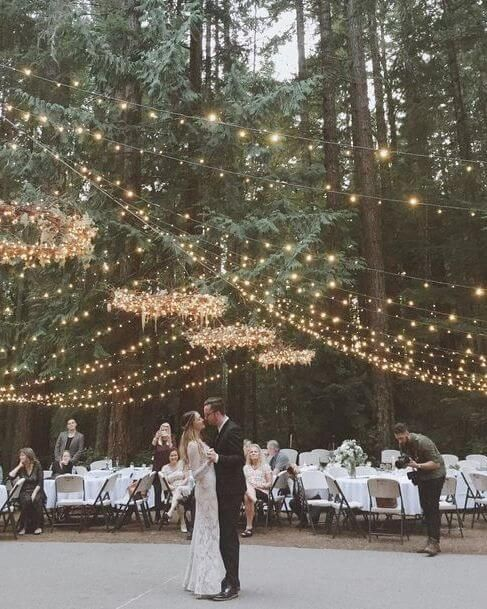 a lovely light canopy with light chandeliers hanging is a pretty and cool idea for an outdoor wedding