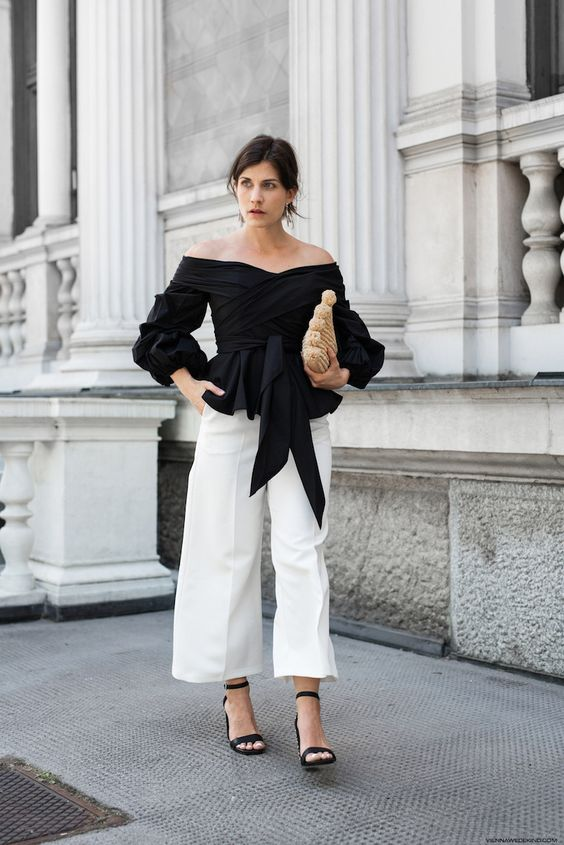 a monochromatic look with an off the shoulder black draped blouse, white wideleg pants, black heels and a woven clutch