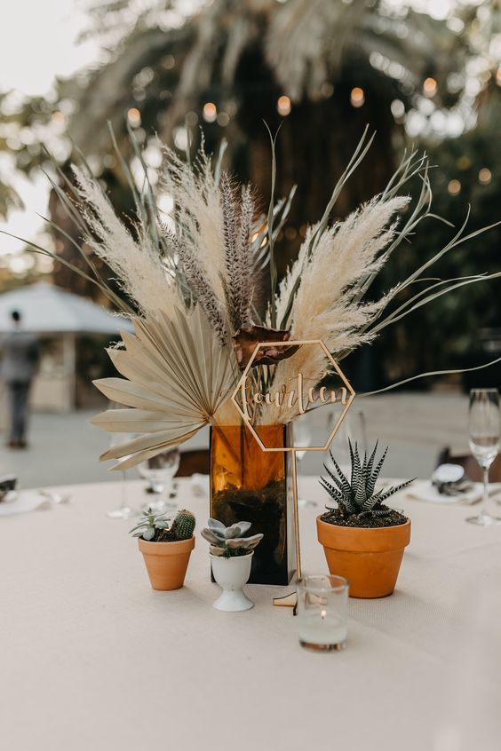 a pretty and catchy wedding centerpiece of a brwon glass vase, pampas grass, fronds, lavender, greenery and potted succulents and cacti