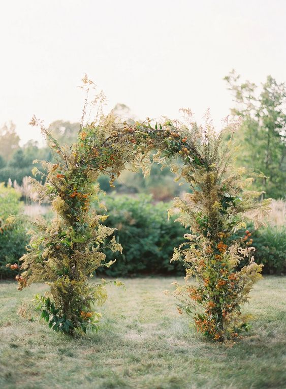 a pretty greenery wedding arch decorated with dried blooms and fruits is a lovely idea for a 70s wedding