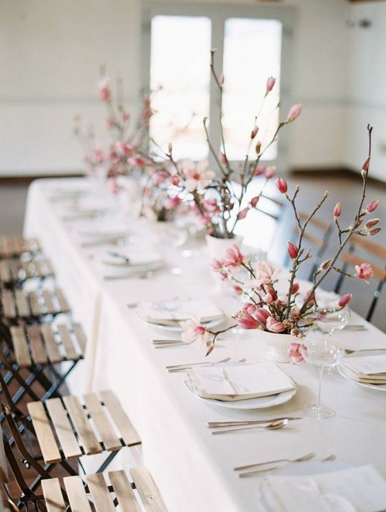 a romantic spring Scandinavian tablescape with pink cherry blossom, white porcelain and linens, neutral cutlery