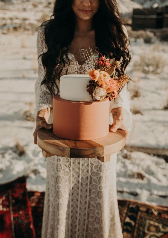 a stylish boho wedding cake with a white and rust tier, with bright orange blooms and greenery is amazing