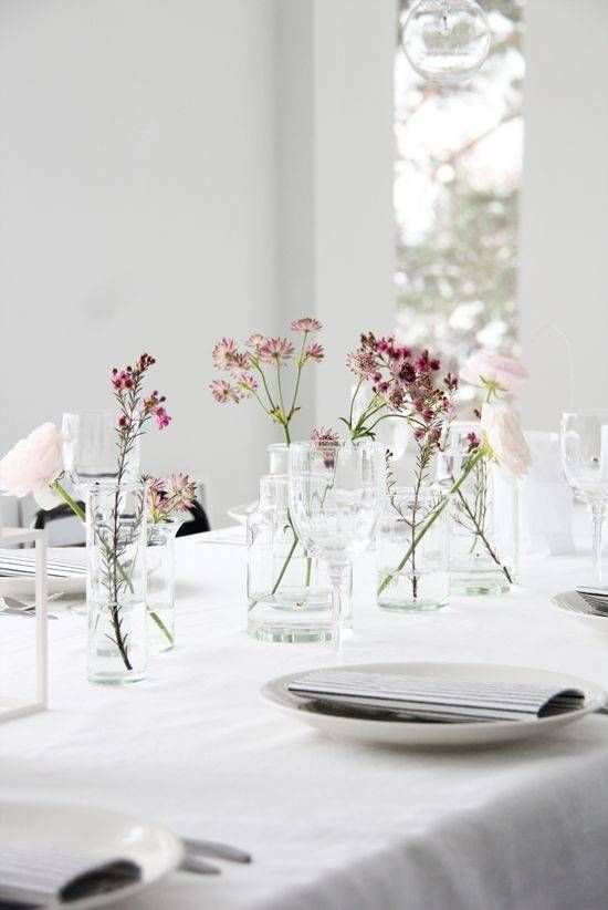a Scandinavian neutral table setting with neutral linens and porcelain, wildflowers in clear vases is chic and simple