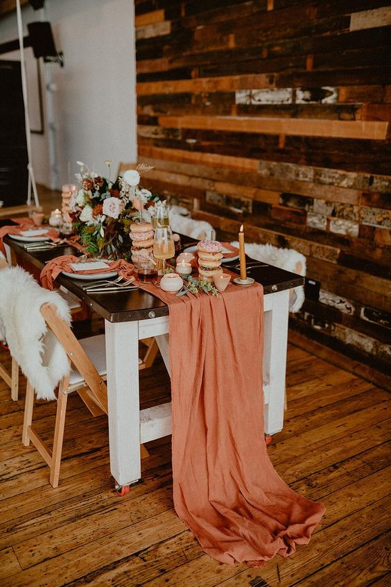 a bold and cool wedding tablescape with a rust table runner, bright florals, rust napkins and candles