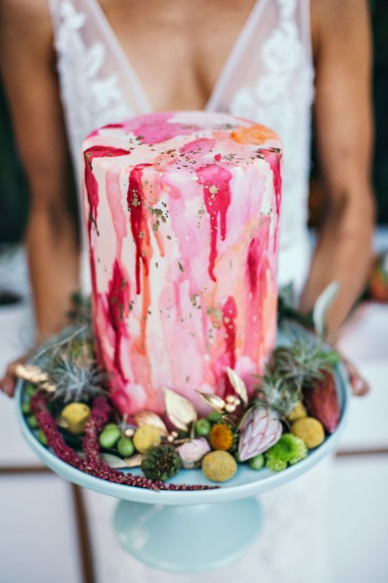 a bright watercolor wedding cake with drip and gold leaf surrounded by greenery and blooms is a lovely idea to try