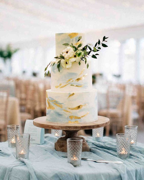 a coastal wedding cake with gold and blue brushstrokes plus some neutral blooms and greenery is a beautiful idea
