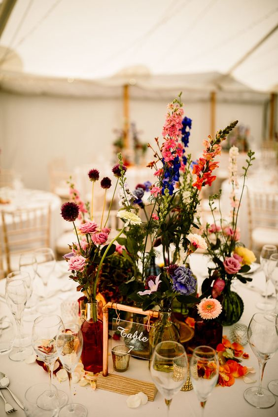 a colorful boho cluster wedding centerpiece of bold blooms and greenery in bottles and vases, petals on the table and a cool table number