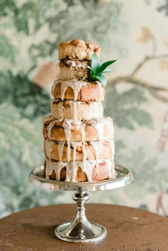 a giant stack of giant cinnamon rolls with cream cheese icing and a touch of greenery for a spring brunch wedding