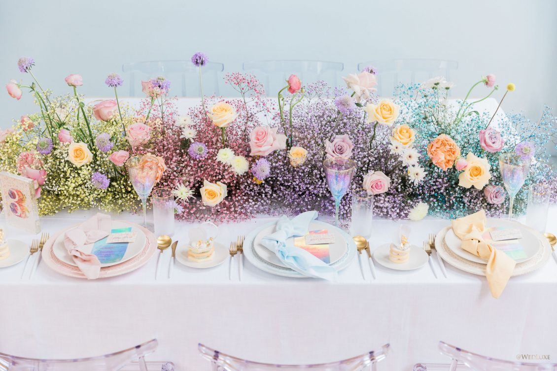 a gorgeous colorful baby's breath table runner with peachy and lilac blooms and pastel plates and iridescent glasses