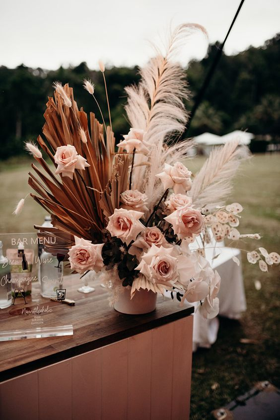 a gorgeous wedding centerpiece with pampas grass, blush roses, fronds and some foliage is wow