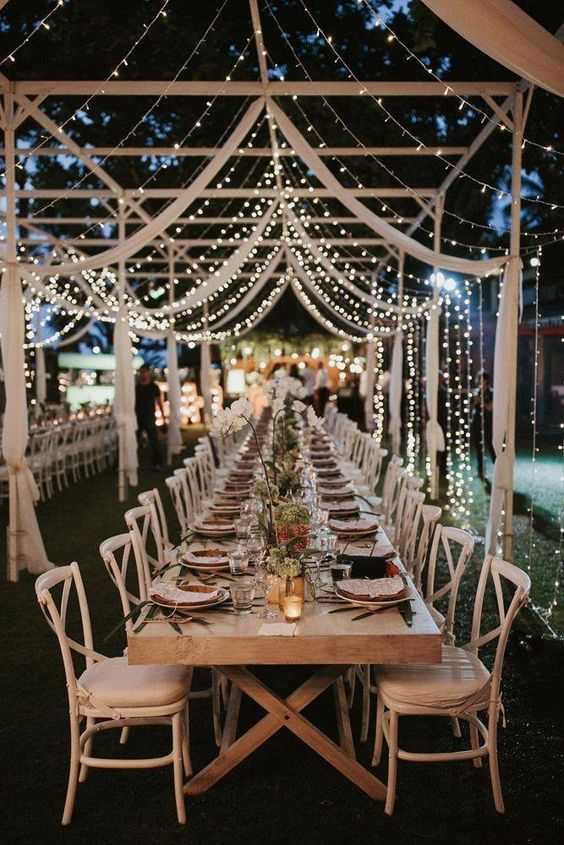 a lovely neutral farmhouse wedding reception space with a trestle table, neutral chairs, a canopy of lights and white fabric