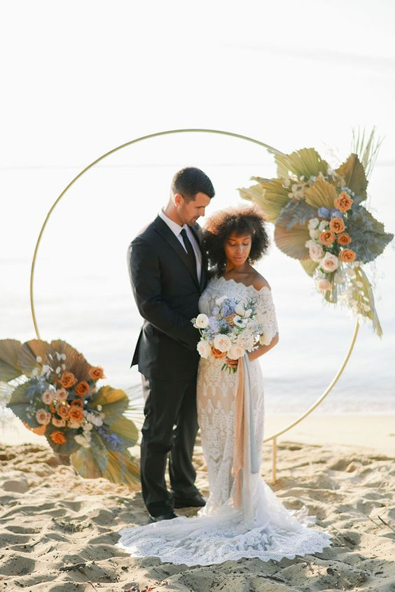 a round wedding arch with dried palm leaves, orange, blush and blue flowers and some foliage for a boho beach wedding