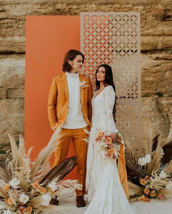 a bold 70s inspired wedding backdrop with an orange and a grey laser cut part, dried grasses and leaves plus bold blooms