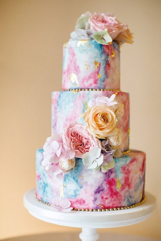 a bright watercolor wedding cake with gold beads, fresh blooms in pastel shades is a pretty and whimsical idea
