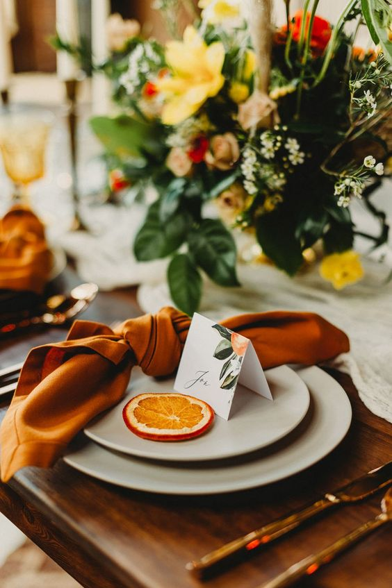 a bright wedding place setting wiht a rust napkin, gold cutlery, dried citrus, a pretty card and a bold floral centerpiece