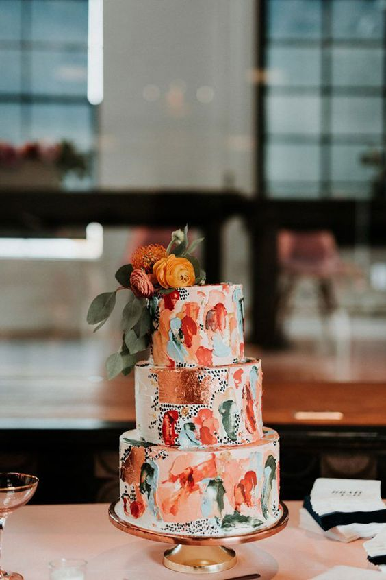 a colorful and abstract brushstroke wedding cake with copper leaf, black polka dots and bold blooms