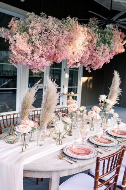 a lovely boho wedding tablescape accented with a pink baby's breath installation looks very chic and bold