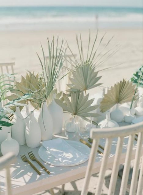 a lovely cluster wedding centerpiece of white bottles, with greenery and fronds is a stylish and cool idea