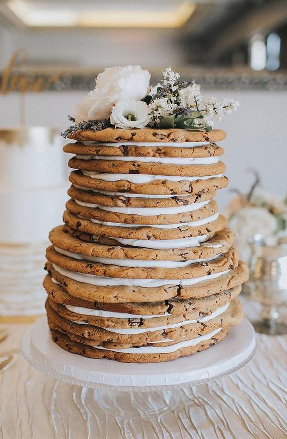 a relaxed cookie wedding cake with fresh blooms and greenery on top is a very cool idea for a laid-back wedding