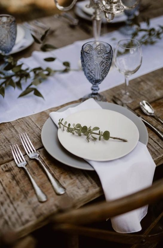 a simple and cool Nordic wedding tablescape with white linens, grey napkins, greenery, blue glasses is very chic