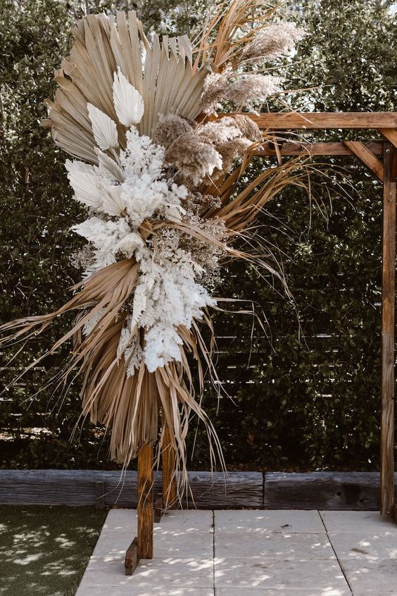 a statement boho wedding arch with dried fronds, white blooms and white fronds and some pampas grass
