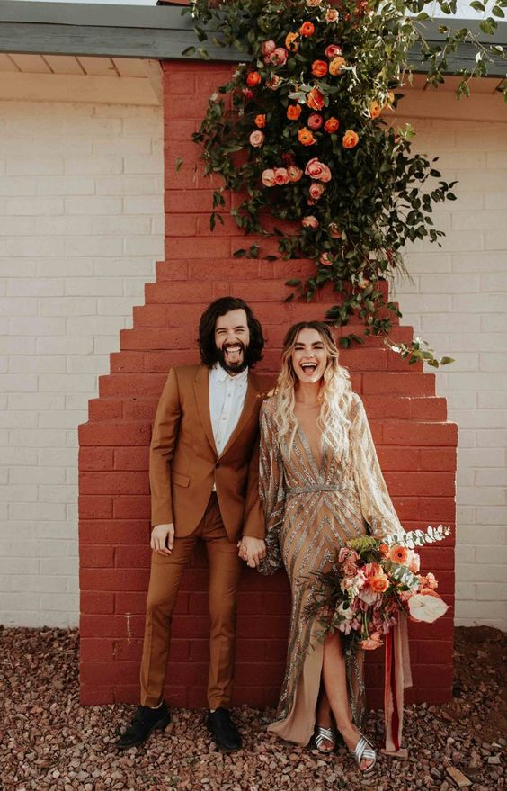 a stylish rust-colored suit, a white shirt and black shoes for a desert or fall boho wedding
