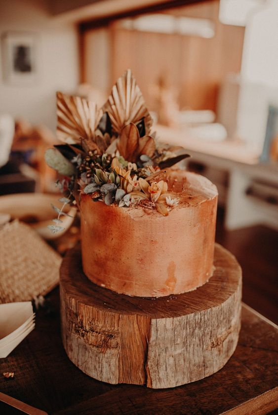a textural rust wedding cake with fresh rust and orange blooms, greenery and copper fronds for a boho wedding