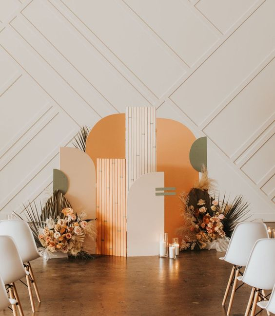 a bold and catchy color block wedding backdrop, lush pastel blooms, fronds and foliage and candles