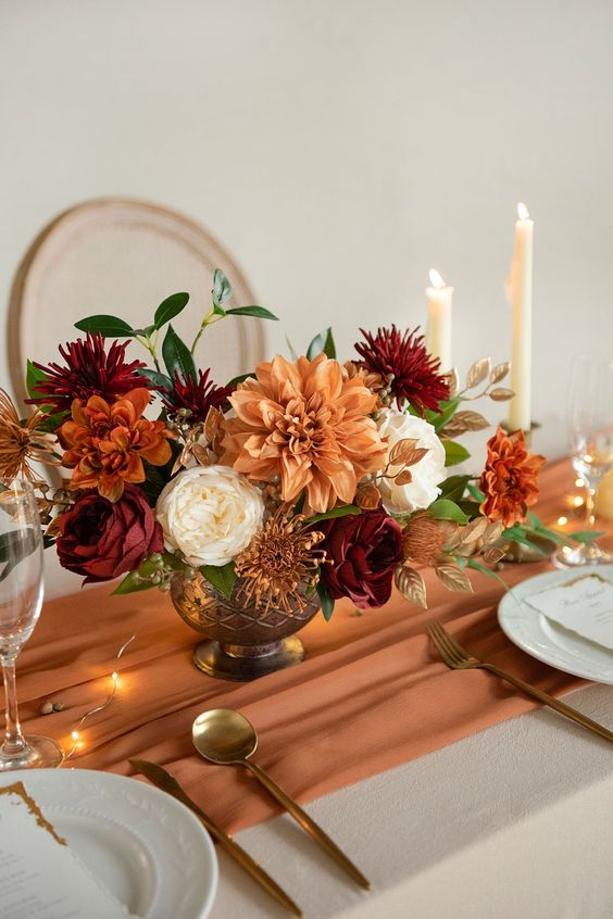 a bright wedding table setting with a rust table runner, rust, burgundy and white blooms, leaves and candles