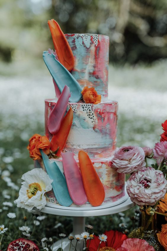 a colorful and artful wedding cake with watercolor tiers, colorful petals, polka dots and fresh blooms