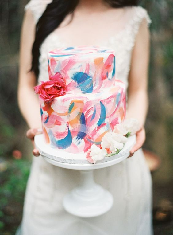 a colorful brushstroke wedding cake in orange, blue, pink and red decorated with fresh blooms for a summer wedding