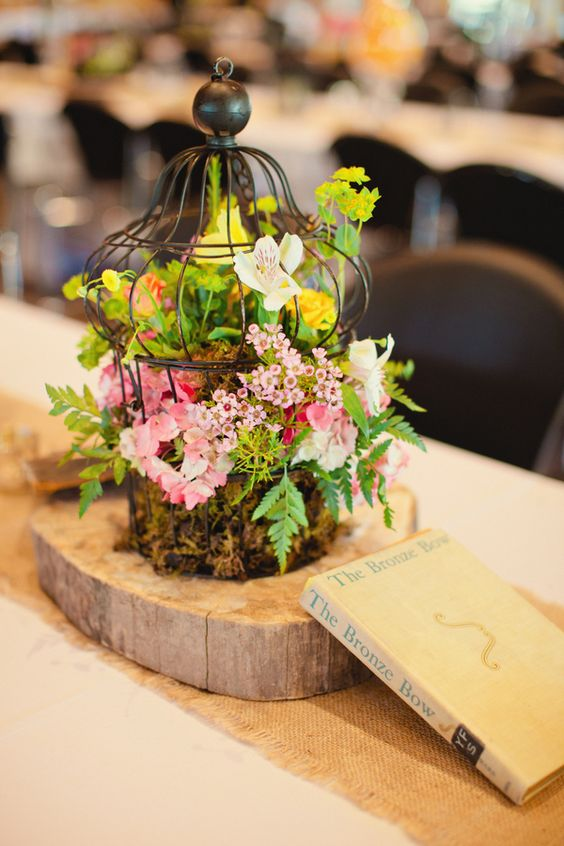 20 a fairy-tale wedding centerpiece of a wood slice and a decorative cage filled with moss, greenery and pink blooms plus a vintage book