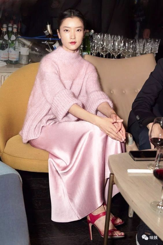 a feminine and tender outfit idea with a pink silk dress, an oversized turtleneck sweater and fuchsia high heels