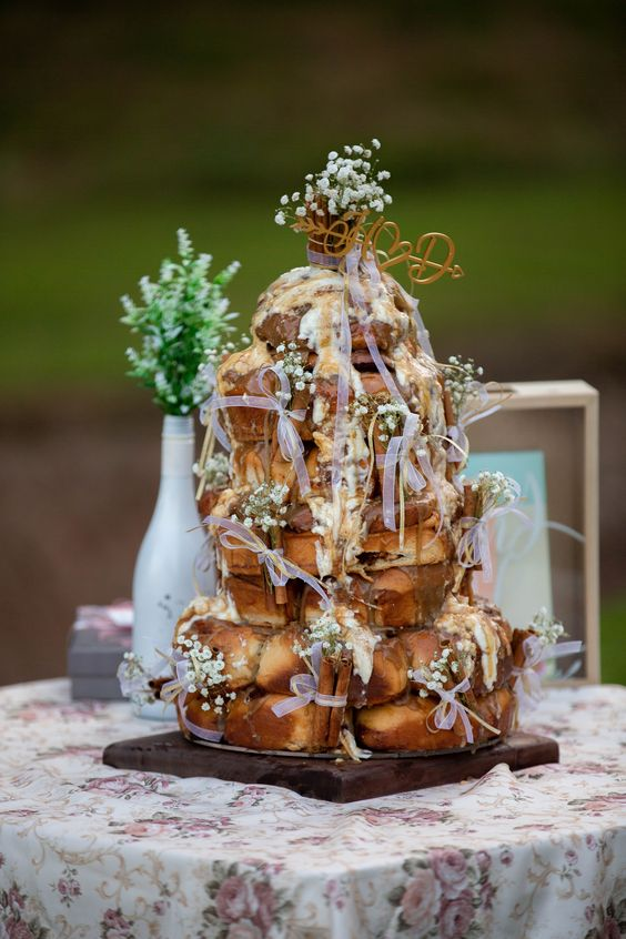 a jaw-dropping cinnamon roll wedding cake with baby's breath, cinnamon sticks, ribbon bows and a small calligraphy topper