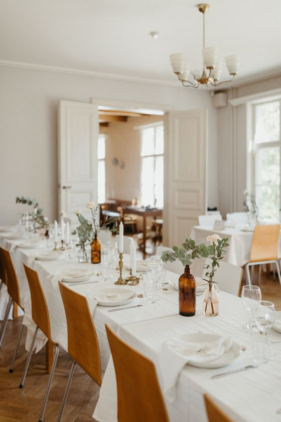 a simple and cute Nordic tablescape with white linens, greenery and blush roses, white plates and simple glasses