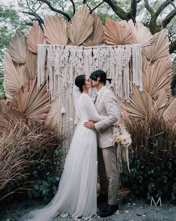 a boho desert wedding backdrop of dried fronds, macrame and greenery growing by it is a chic idea